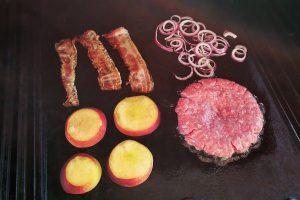 Pfirsich, Ziebeln, Bacon und Fleisch auf dem Grill