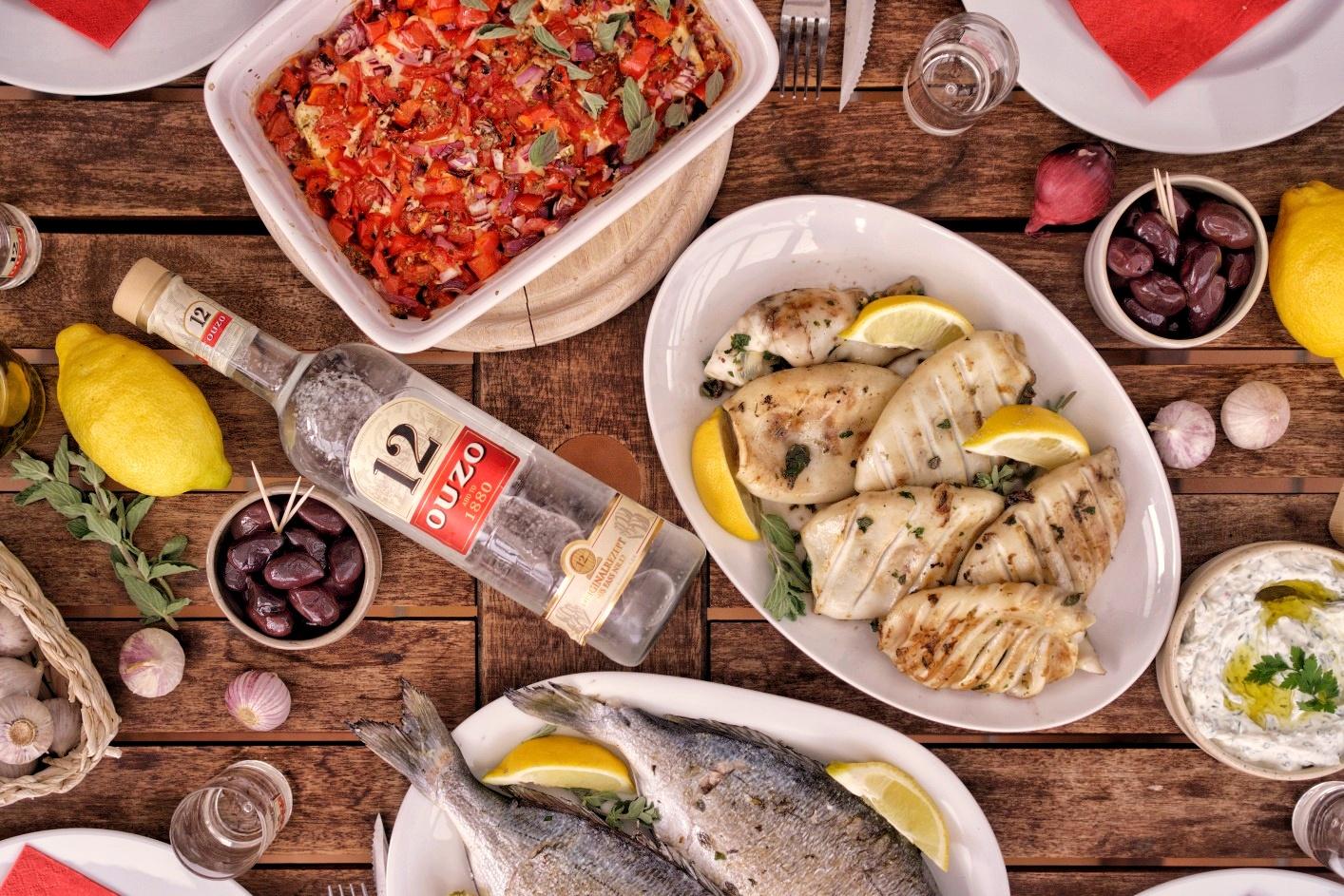 Tisch mit gegrillten Calamari, Doraden, Oliven, gebackenenem Feta und Ouzo 12